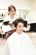 仕上がりを見せる美容師1